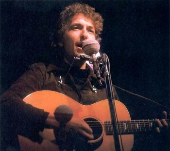 Dylan on stage with an accoustic guitar